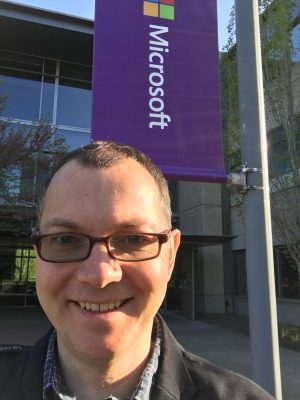 Picture of Tom in front of a Microsoft Banner